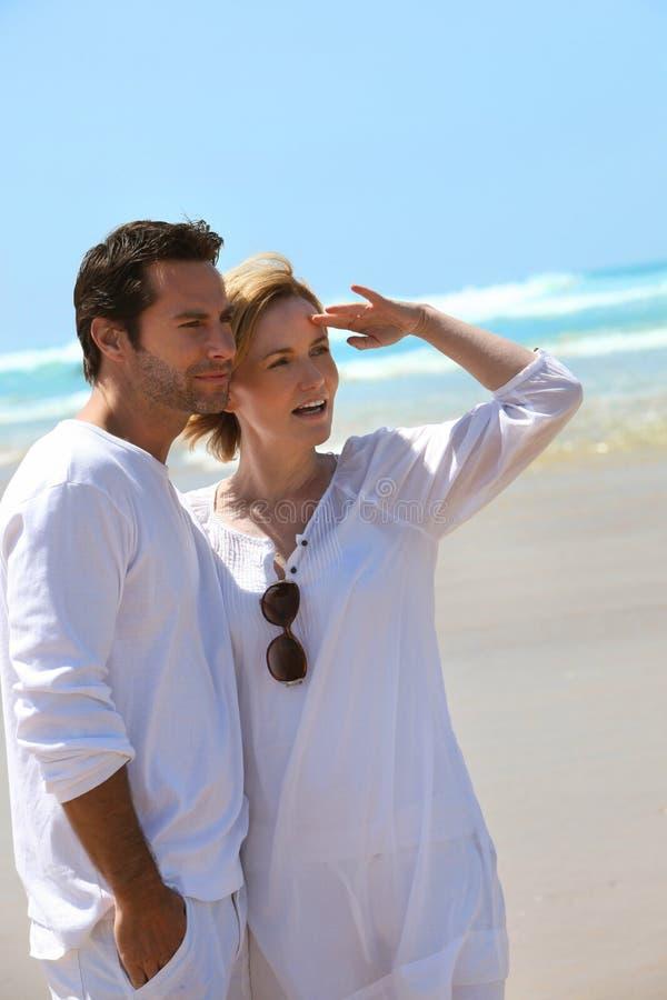 Couple stood on the beach stock photography