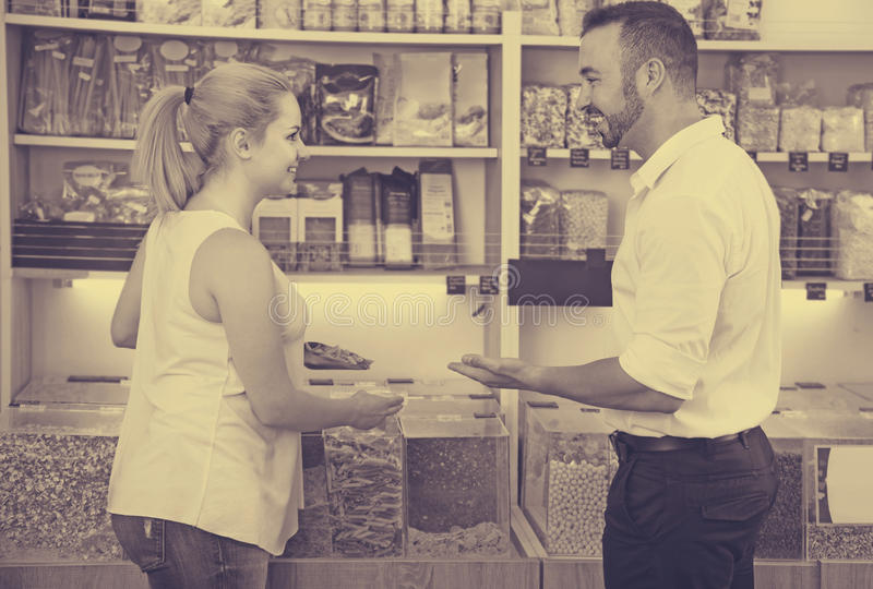 Couple in store of ecological goods. Positive smiling young couple selecting various groats in the store with ecological goods royalty free stock photo