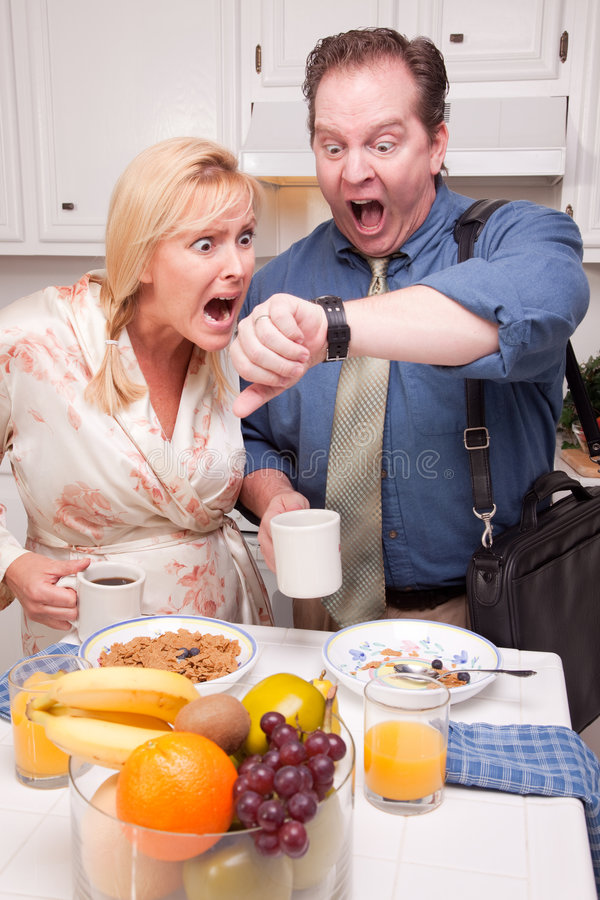 Couple Stressed Out in Kitchen Late for Work stock images