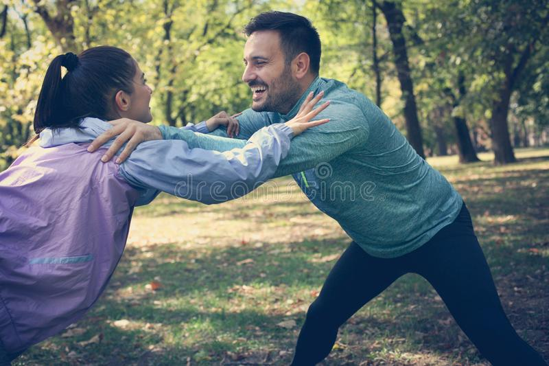 Couple stretching in park. Young couple working exercise togethe stock image