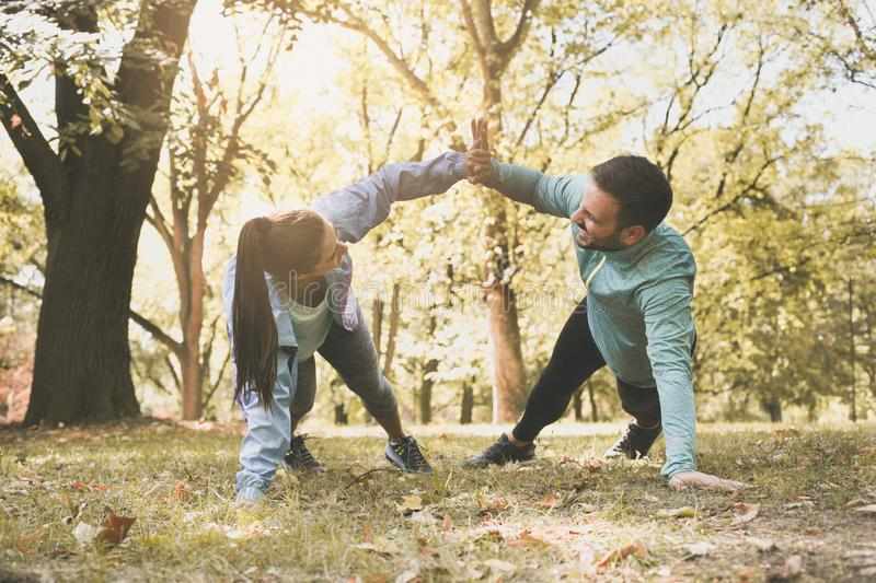 Couple stretching in park. Young couple working exercise togethe stock photography