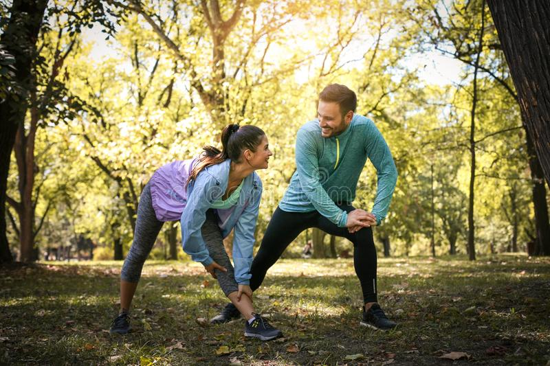 Couple stretching in park. Young couple working exercise togethe. R. Nature royalty free stock photography