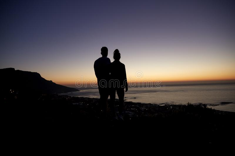 Couple strolling by the sea at sunset on a beach, silhouette royalty free stock photos