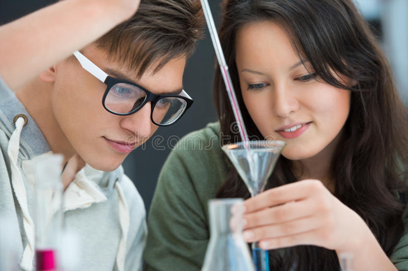 Couple of students working at chemistry classroom. High School students. Couple of students working at chemistry class: mixing reagent liquids and using stock photos
