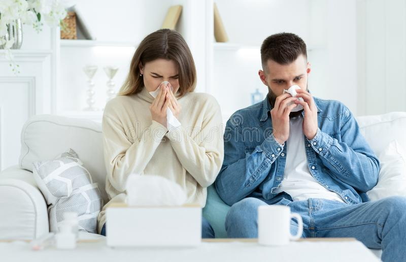 Couple Suffering From Cold, Blowing Noses And Sneezing. Sitting On Sofa At Home stock photography
