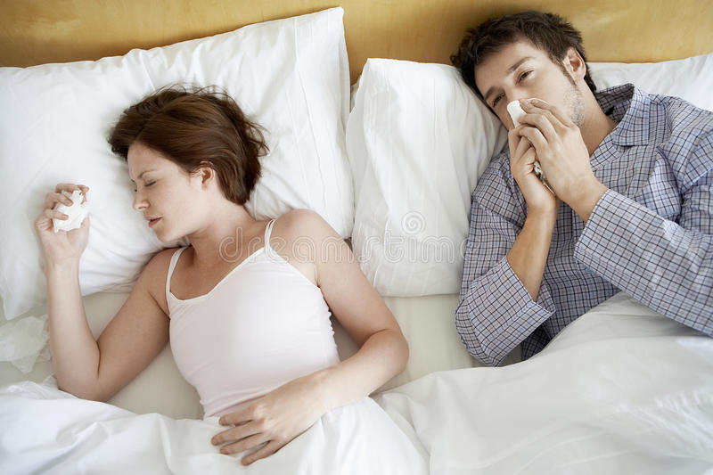 Couple Suffering From Colds In Bed