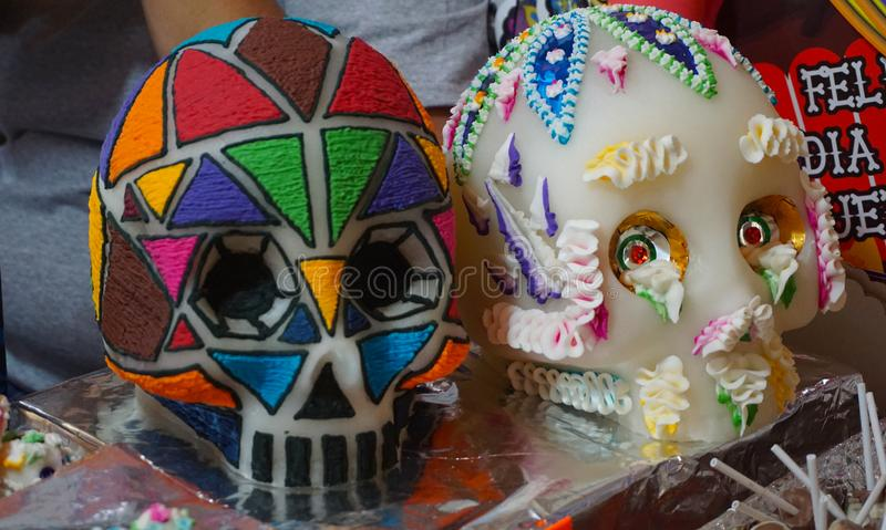 Big sugar skulls. Couple of sugar skulls handcrafted with different decorations also made of sugar, one with a classic stile of curly shapes and other with royalty free stock photos