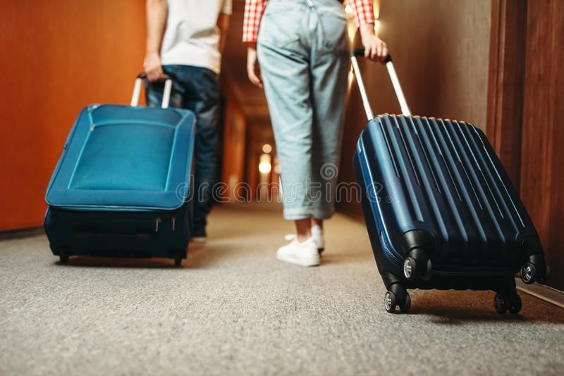 Couple with suitcase walking by the hotel corridor stock photo