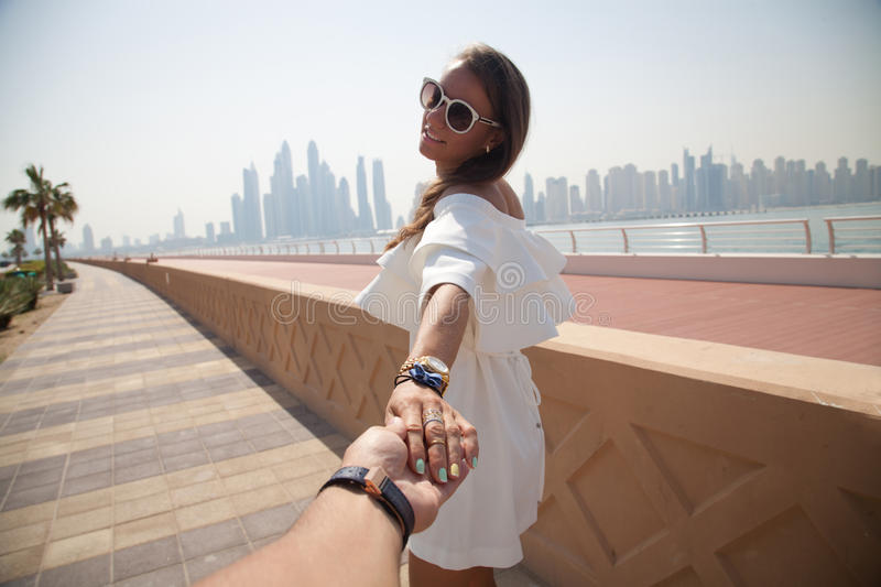 Couple summer vacation travel. Woman walking on romantic honeymoon promenade holidays holding hand of husband following her, view from behind. Couple summer stock photography