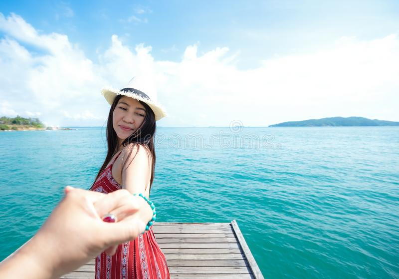 Couple summer vacation travel, Woman walking on romantic honeymoon and relax on the wood bridge near beach in holidays holding han royalty free stock photo