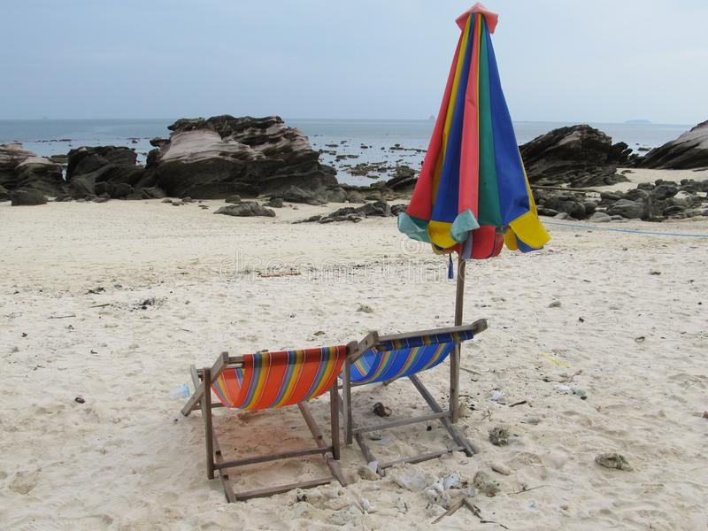 Couple of sun loungers and a folded beach tent stand on the shore of a deserted beach stock photos