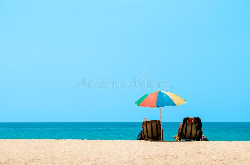 Couple sunbathing and relaxing on beach chairs. Sands and sea view, Summer background stock photo