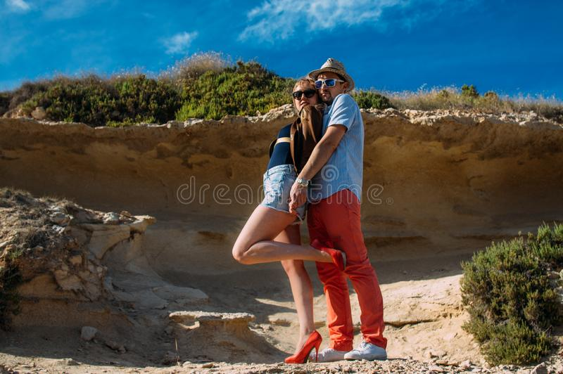 Couple in sunglasses embrace in the day in the hills royalty free stock photography