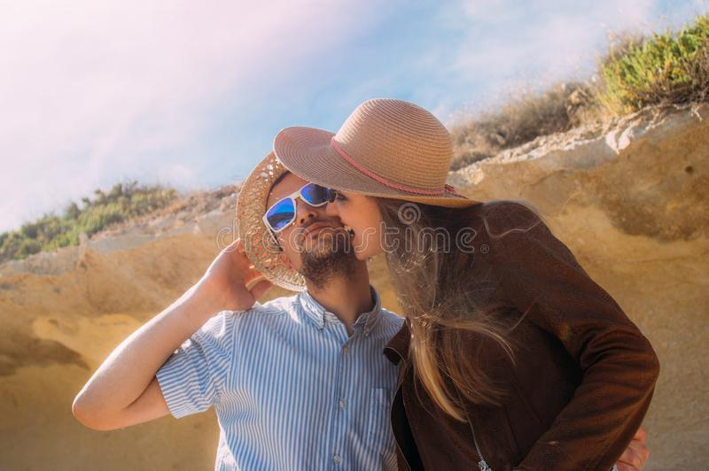 Couple in sunglasses embrace  in the day in the hills royalty free stock image