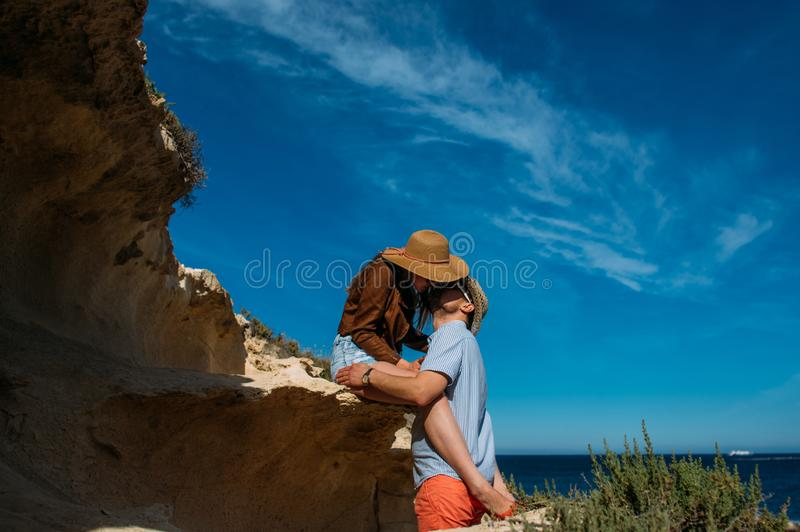 Couple in sunglasses embrace and kissing in the day in the hills royalty free stock image