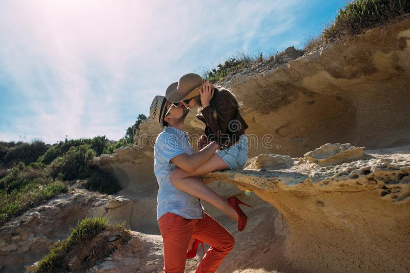 Couple in sunglasses embrace and kissing in the day in the hills stock photos
