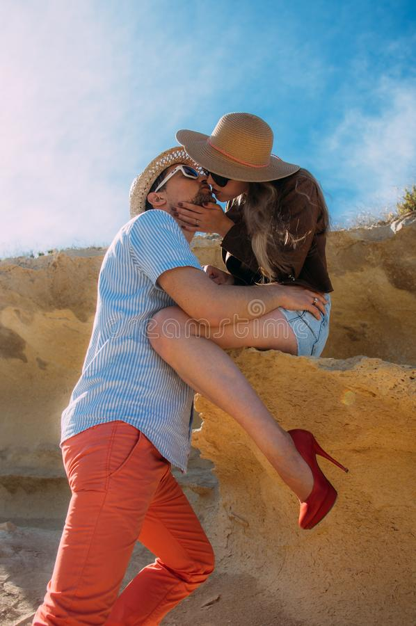 Couple in sunglasses embrace and kissing in the day in the hills royalty free stock photos