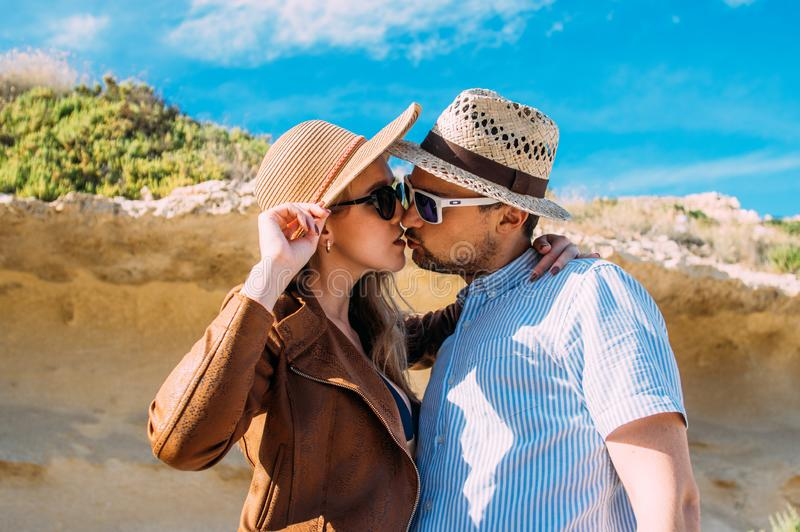 Couple in sunglasses embrace and kissing in the day in the hills royalty free stock photography