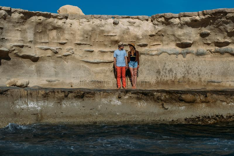 Couple in sunglasses staying on the coastline, looking to eachother royalty free stock image