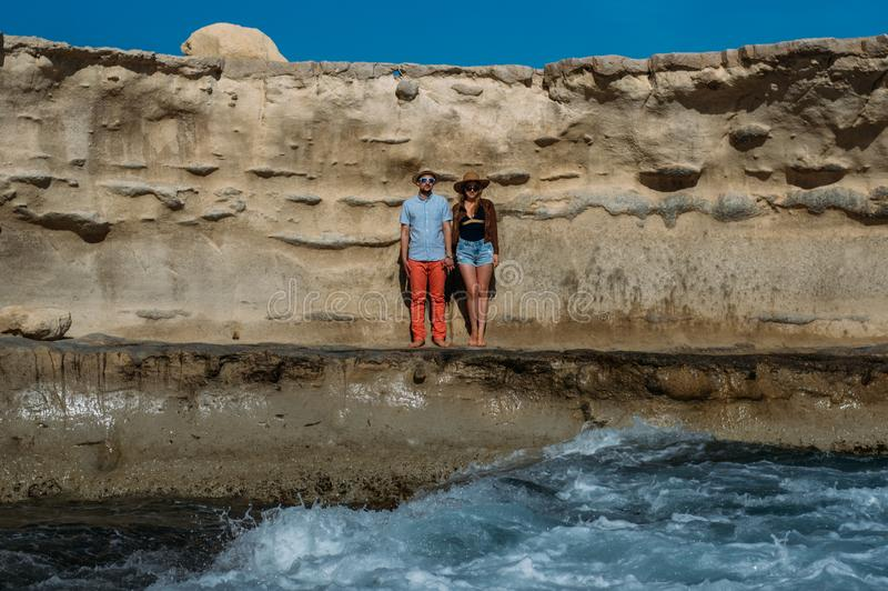 Couple in sunglasses staying on the coastline stock photo