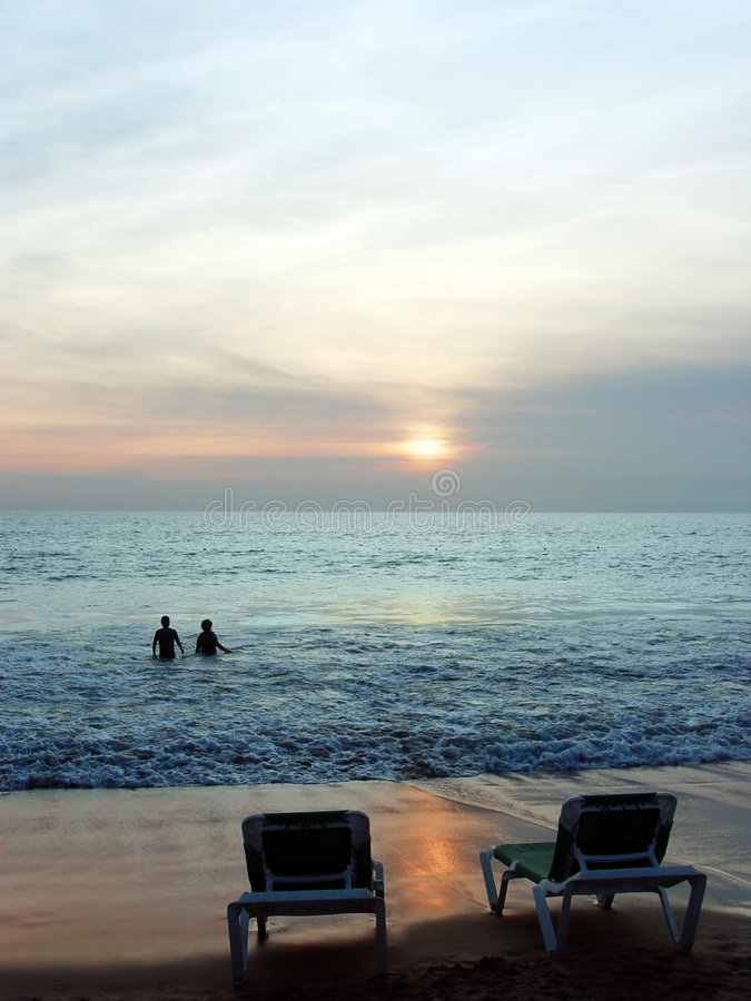 Couple at sunset. Couple swimming in the ocean at sunset