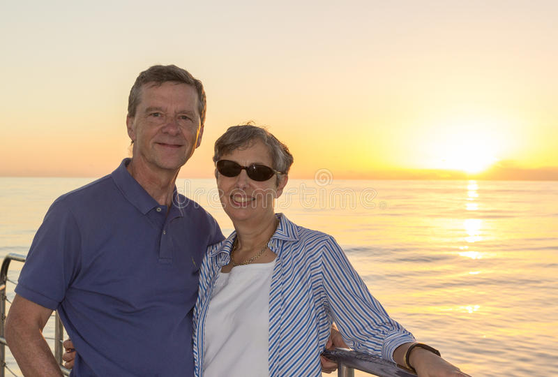 Couple on sunset cruise Kauai. Middle aged couple on an ocean sunset cruise and leaning against the railings. Smiling and facing the camera royalty free stock image