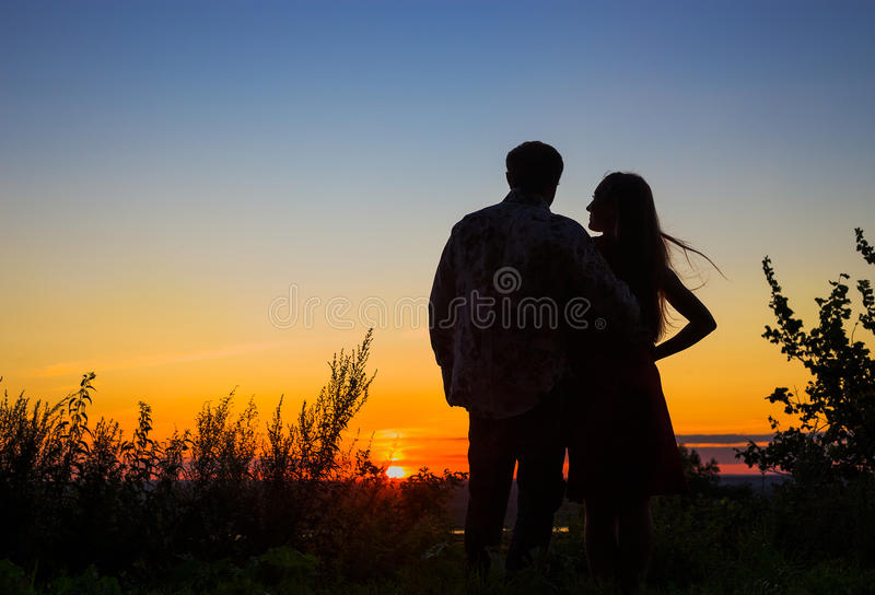 Couple on sunset. Silhouette of young couple meets a beautiful sunset over the field from high hill