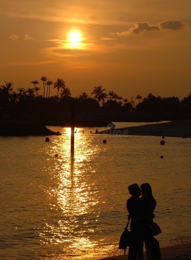 Couple at sunset on the Singapore beach stock photo