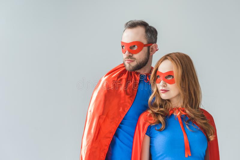 Couple in superhero costumes standing together and looking away. Isolated on grey royalty free stock images