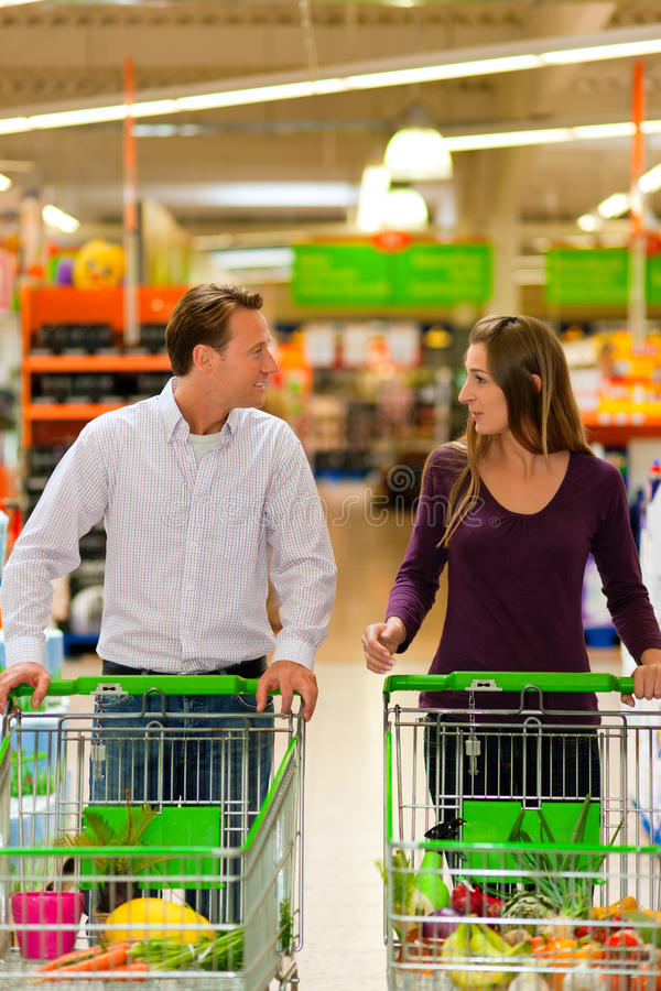 Couple in supermarket with shopping cart royalty free stock photo