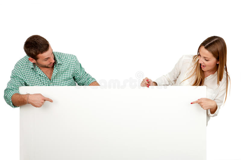 Couple with surprised look holding blank board. stock images
