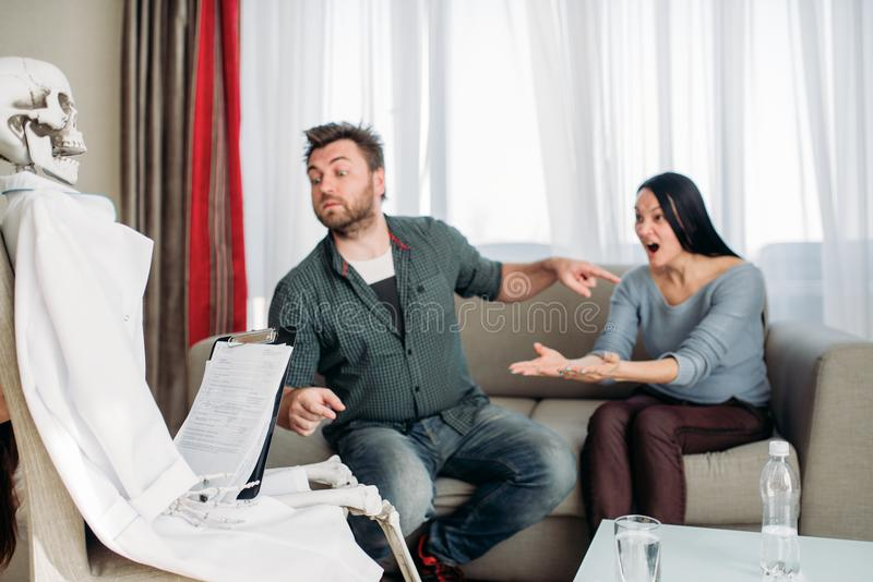 Couple swears at doctor skeleton reception. Family psychology support, humor royalty free stock image