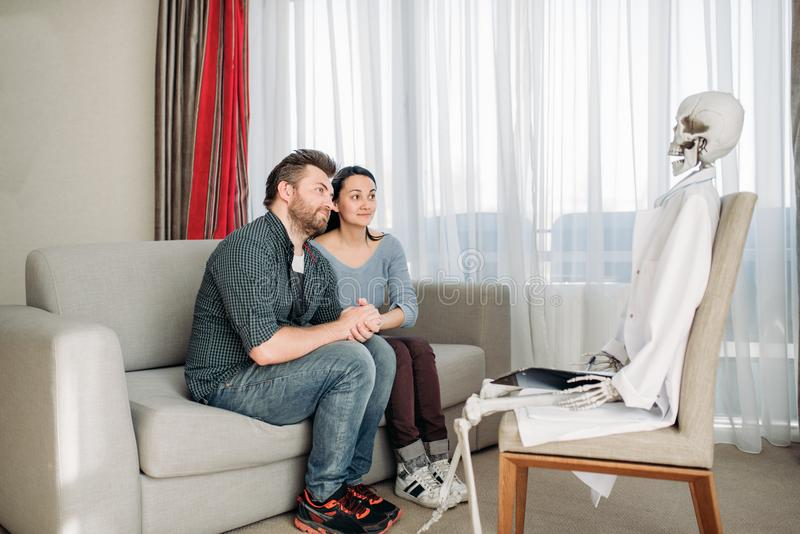 Couple swears at doctor skeleton reception. Family psychology support, humor stock photo