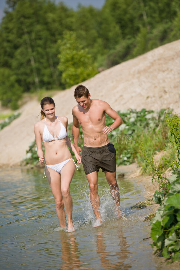 Download Couple In Swimwear Jogging At Lakeside Stock Photo - Image: 15140322