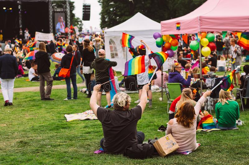 Couple swinging rainbow flags and sitting on the grass on Helsinki Pride festival in stock photos