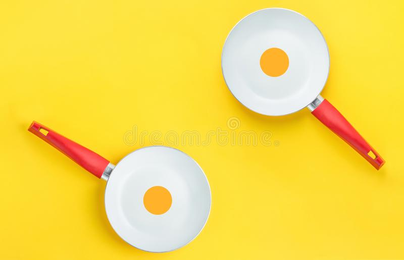 Couple of symmetric white ceramic frying pans with red handle on bright yellow background. Sunny side up fried eggs royalty free stock images