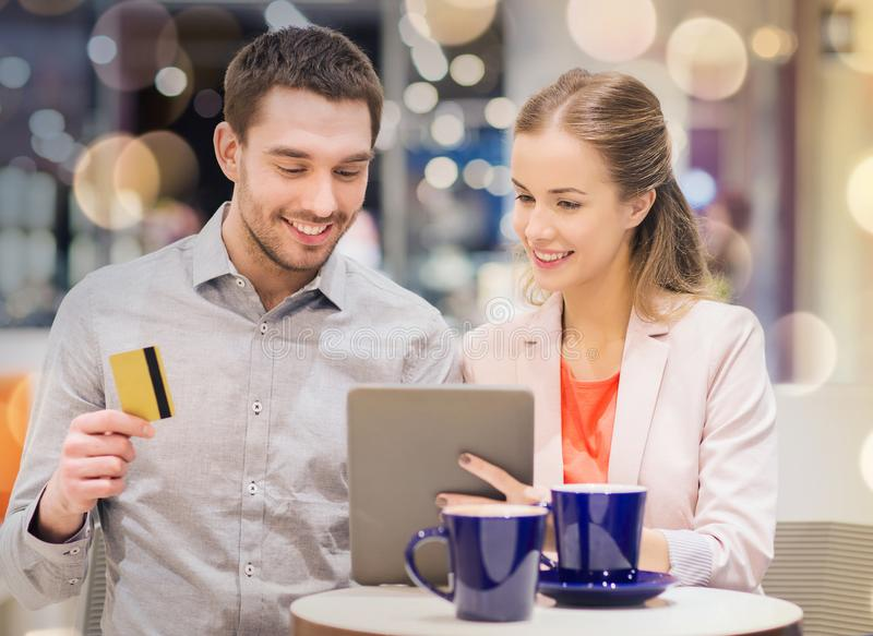 Couple with tablet pc and credit card in mall. Sale, shopping, consumerism, leisure and people concept - happy couple with tablet pc and credit card drinking stock image