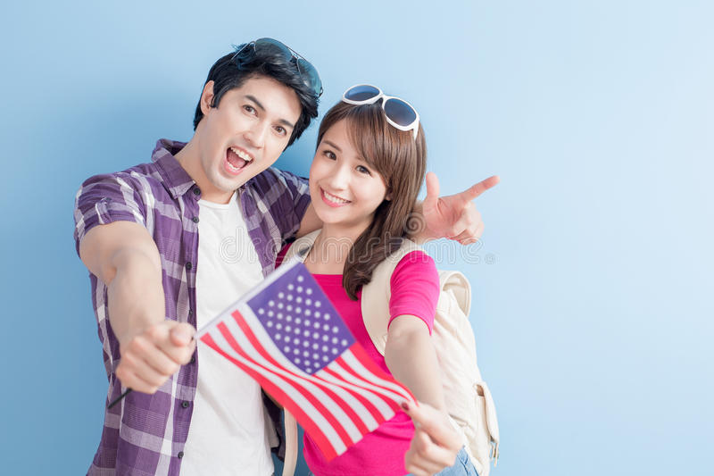 Couple take american flag. Young couple take american flag with blue background royalty free stock photos