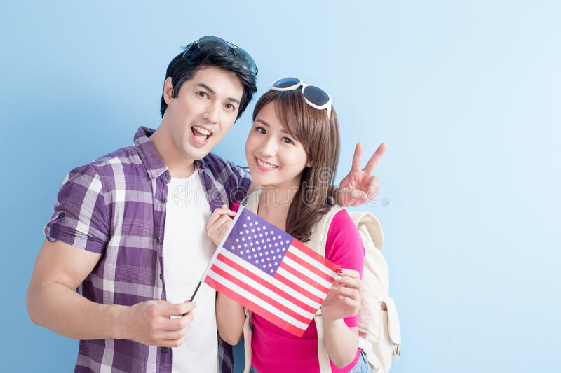 Couple take american flag. Young couple take american flag with blue background stock image