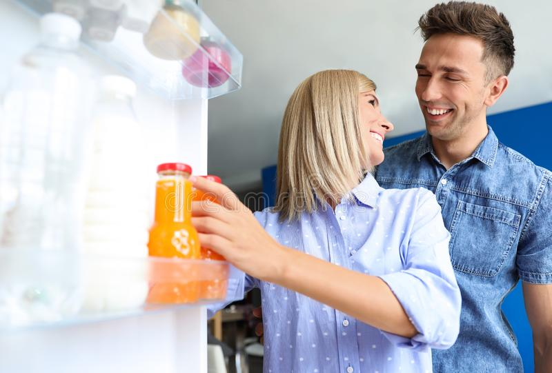 Couple taking bottle with juice out of refrigerator royalty free stock images