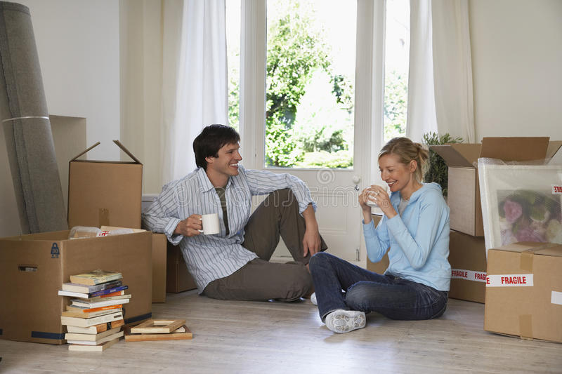 Couple Taking A Break Among Moving Boxes royalty free stock images