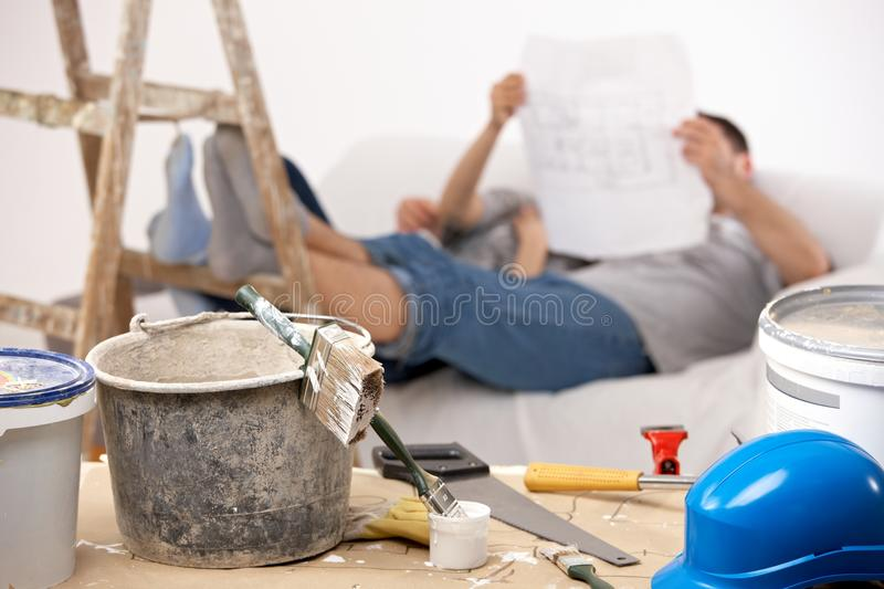 Couple taking break of painting house. Checking on ground plan of house together, focus on painting equipment stock image