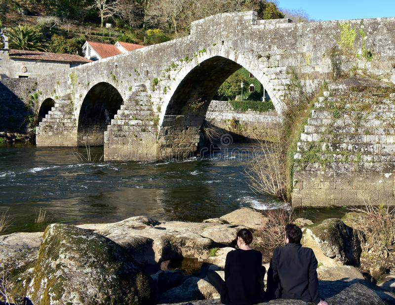 A couple taking a break in a river close to an old stone bridge. Ponte Maceira, Spain, 16 Feb 2019. royalty free stock image