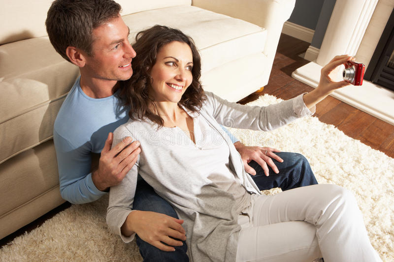 Couple Taking Photograph On Digital Camera At Home stock photos