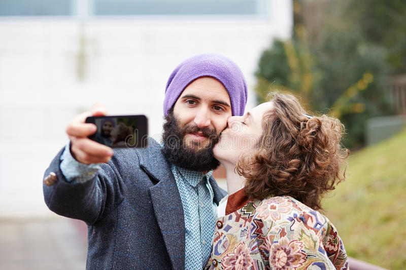 Couple taking a photograph of themselves kissing with a smartphone royalty free stock photo