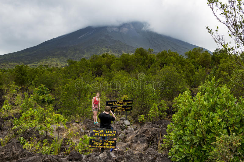 Couple taking a picture with the Arenal Volcano on the background at the Lava Viewpoint in Costa Rica stock photography