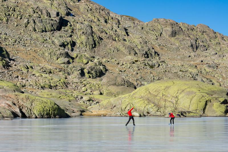 Gredos, Spain. 12-January-2019. Couple taking pictures on a frozen lake in the mountains during a sunny winter day royalty free stock images