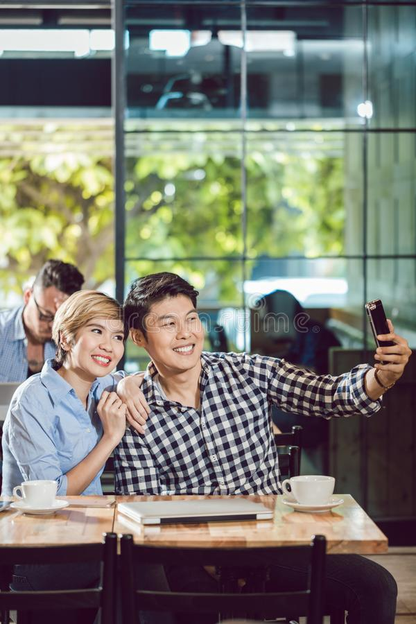 Couple taking self-portrait on mobile stock photography