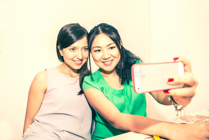 Couple taking selfie on hay. Two girlfriends taking a selfie with smart phone - Happy women having fun at party - Young multiracial couple of girls sending their stock images