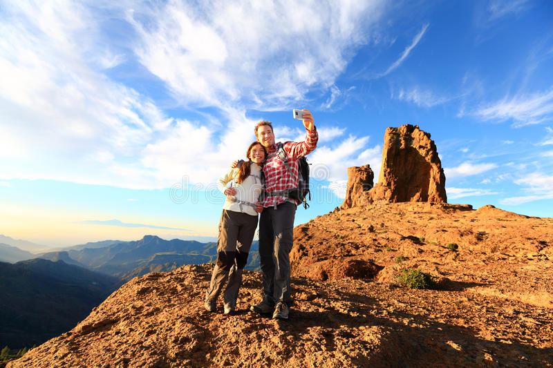 Couple taking selfie hiking in beautiful nature. With smart phone. Happy couple walking enjoying view and taking pictures with smartphone. Man and women by